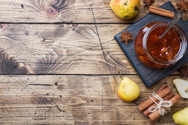 Eigengemaakte perenjam in een kruik en verse peren op een houten achtergrond
