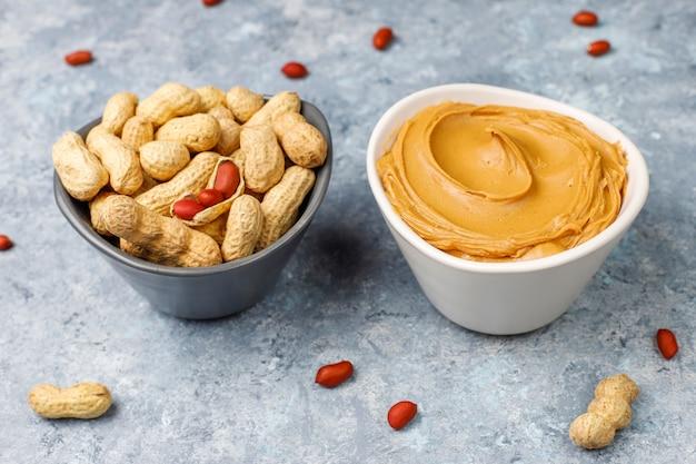 Eigengemaakte pindakaas met pinda's op grijze concrete lijst, hoogste mening