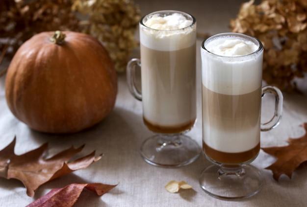 Eigengemaakte pompoen latte in lange glazen en pompoen op een linnentafelkleed. rustieke stijl.