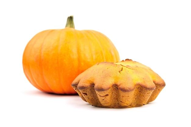 Eigengemaakte pompoencake met verse pompoen die op witte achtergrond wordt geïsoleerd. herfst pompoen bakkerij