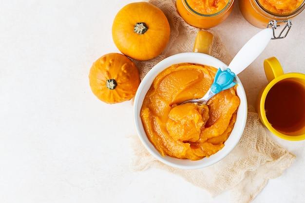 Eigengemaakte pompoenpuree in kom met babylepel en verse pompoenen. het concept van babyvoeding.