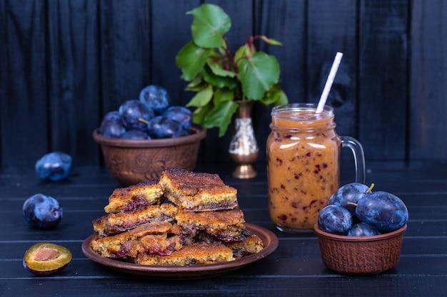 Eigengemaakte pruimentaart in plaat, pruimensmoothies en ruwe blauwe pruimen op zwarte houten