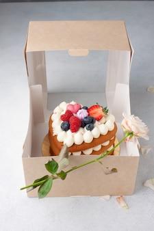 Eigengemaakte rode fluweelcake in hartvorm voor st. valentijnsdag met witte roze bloem