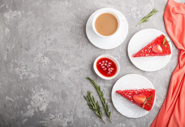 Eigengemaakte rode fluweelcake met melkroom en aardbei met kop van koffie op een grijze concrete achtergrond. bovenaanzicht, kopie ruimte.