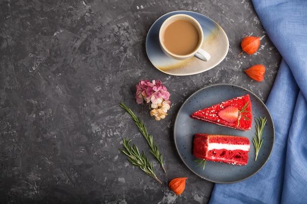 Eigengemaakte rode fluweelcake met melkroom en aardbei met kop van koffie op een zwarte concrete achtergrond. bovenaanzicht, kopie ruimte.