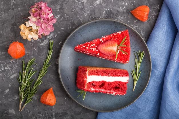 Eigengemaakte rode fluweelcake met melkroom en aardbei met kop van koffie op een zwarte concrete oppervlakte. bovenaanzicht, close-up.