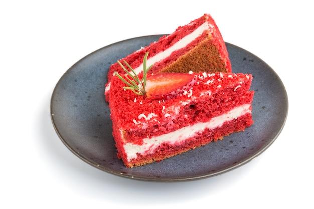 Eigengemaakte rode fluweelcake met melkroom en aardbei op blauwe ceramische geïsoleerde plaat. zijaanzicht, close-up.