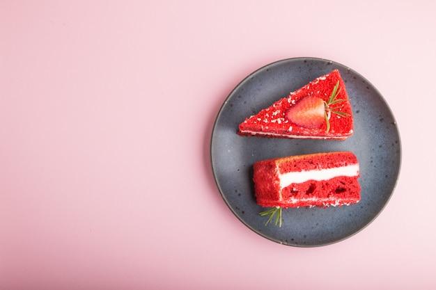 Eigengemaakte rode fluweelcake met melkroom en aardbei op blauwe ceramische plaat die op een roze pastelkleurachtergrond wordt geïsoleerd. bovenaanzicht, kopie ruimte.