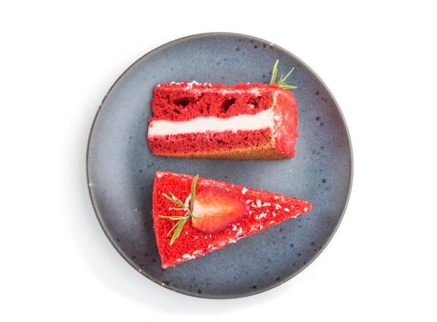 Eigengemaakte rode fluweelcake met melkroom en aardbei op blauwe ceramische plaat die op witte oppervlakte wordt geïsoleerd. bovenaanzicht.