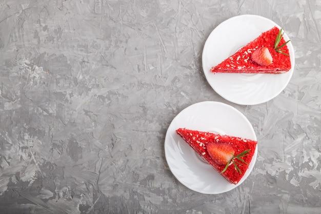 Eigengemaakte rode fluweelcake met melkroom en aardbei op een grijze concrete achtergrond. bovenaanzicht, kopie ruimte.