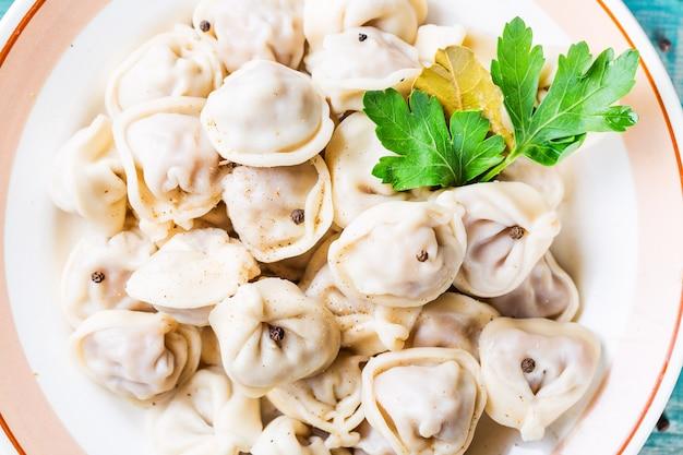 Eigengemaakte russische pelmeni van vleesbollen met peterselie in plaat dichte omhooggaand,