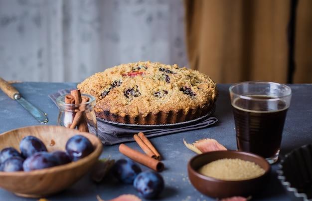 Eigengemaakte rustieke pruimcake op donkere concrete achtergrond. zoete vruchten taart.