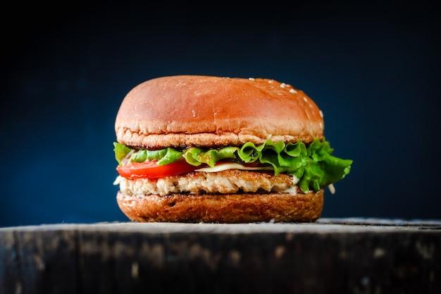 Eigengemaakte smakelijke chickenburger op zwarte achtergrond.