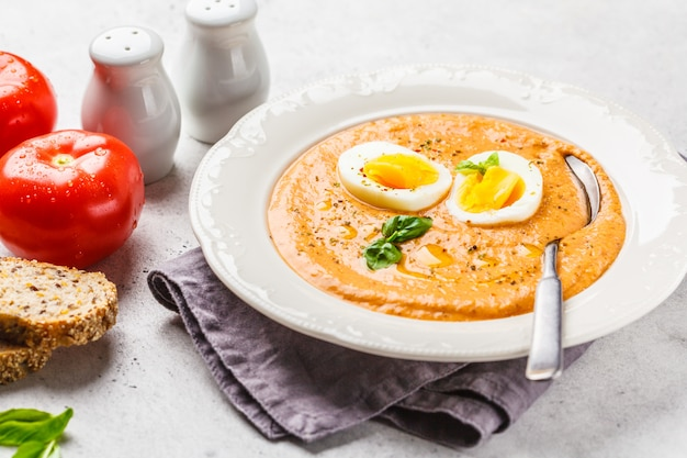 Eigengemaakte spaanse salmorejo met ei in witte plaat.