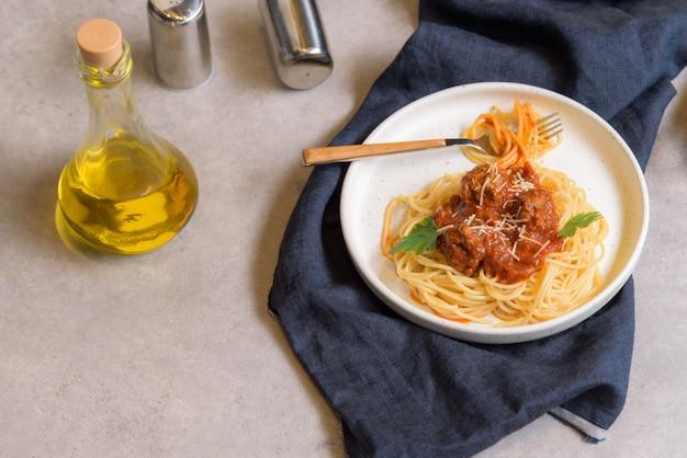 Eigengemaakte spaghetti of deegwaren met vleesballetje en kaas in tomatensaus die in een witte schotel wordt geplaatst.