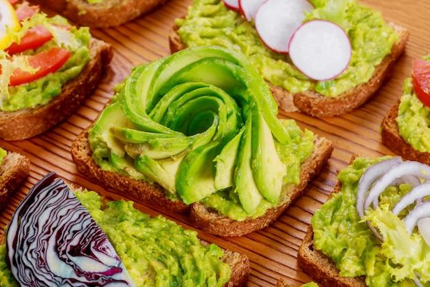 Eigengemaakte toostsandwich met avocado en jam op houten raads gezond voedsel