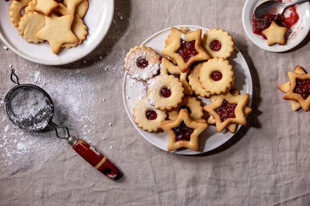 Eigengemaakte traditionele linz-zandkoekkoekjeskoekjes met rode jam en suikerglazuursuiker op ceramische plaat over linnen tafelkleed. plat leggen, ruimte