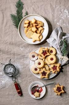 Eigengemaakte traditionele linz-zandkoekkoekjeskoekjes met rode jam en suikerglazuursuiker op ceramische plaat over linnen tafelkleed.