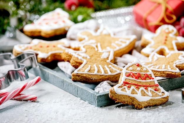 Eigengemaakte traditionele peperkoekkoekjes van kerstmis met versierd suikerglazuur. gingerbread man, engel, bel met xmas decoraties over witte bokeh oppervlak.