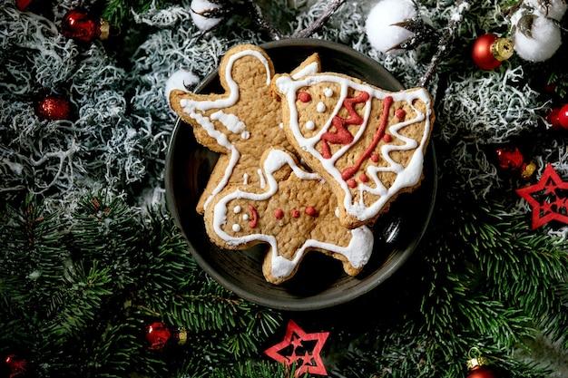 Eigengemaakte traditionele peperkoekkoekjes van kerstmis met versierd suikerglazuur. gingerbread man, engel, bel op keramische plaat met kerstversieringen en dennenboom. plat leggen
