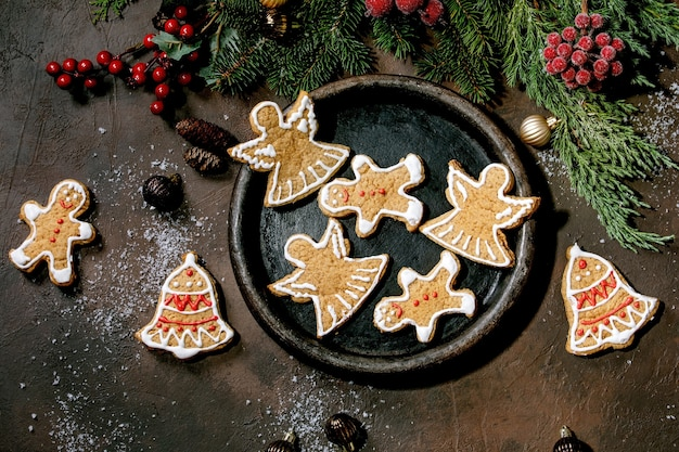 Eigengemaakte traditionele peperkoekkoekjes van kerstmis met versierd suikerglazuur. gingerbread man, engel, bel op keramische plaat met kerstversieringen over donkere ondergrond. plat leggen