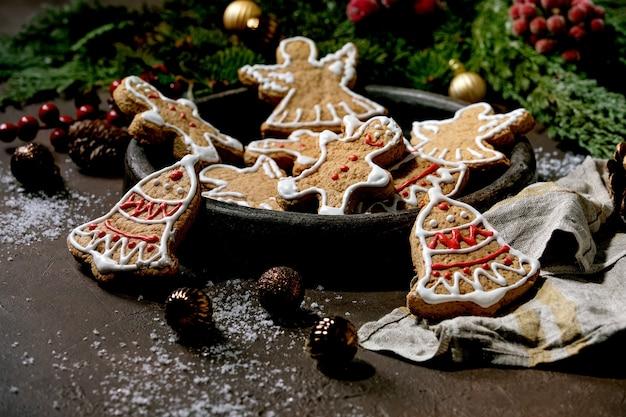 Eigengemaakte traditionele peperkoekkoekjes van kerstmis met versierd suikerglazuur. gingerbread man, engel, bel op keramische plaat met kerstversieringen over donkere ondergrond.