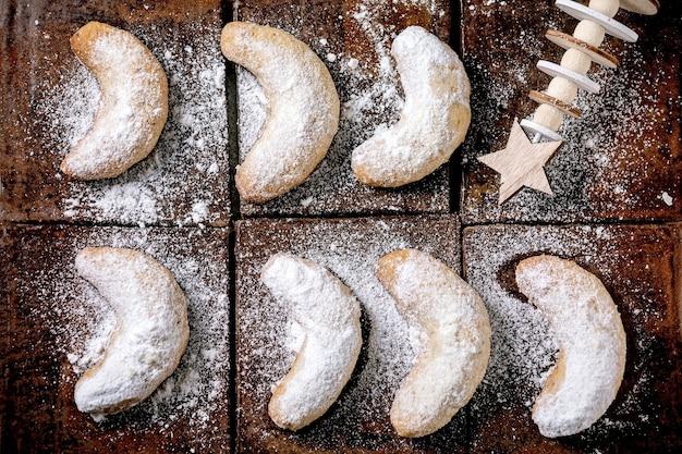 Eigengemaakte traditionele vanille-crescents van de koekjesdeegkoekjes van kerstmis met suikerglazuursuiker met houten kerstmisdecoratie over donkere ceramiektegeloppervlakte. bovenaanzicht