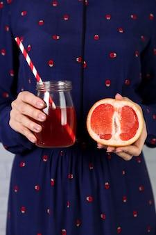 Eigengemaakte verse grapefruit juice en een gesneden grapefruit