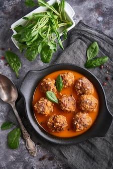 Eigengemaakte vleesballetjes met tomatensaus en spinazie in een plaat, hoogste mening