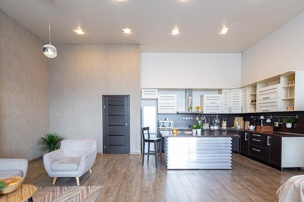 Eigentijds gewoon ontwerp van appartement in zachte, warme kleuren. eenvoudig meubilair. lichte grote kamer met zonlicht. dag. betegelde bruine vloer en witte muren.