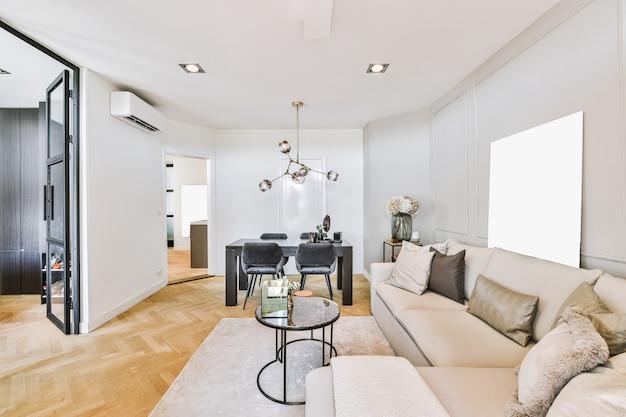Eigentijds interieur van woonkamer met zachte bank en glazen tafel in appartement