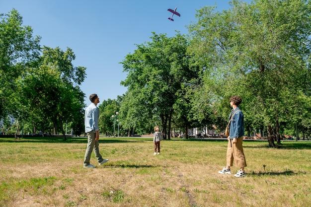 Eigentijds jong gezin van drie spelen met speelgoed vliegtuig op groot groen gazon tussen bomen terwijl ze tijd doorbrengen in park in de zomer