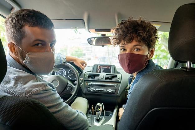 Eigentijds jong stel in spijkerjasjes en beschermende maskers die in de auto zitten en naar u kijken terwijl u naar huis of naar de supermarkt rijdt