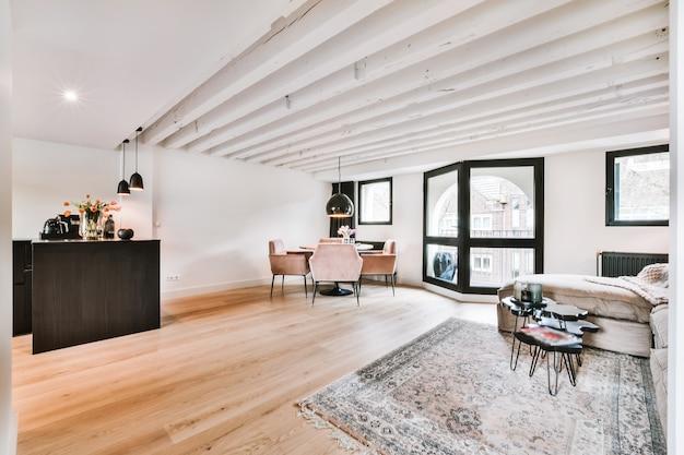 Eigentijds luxe design van woonkamer met open keuken en eettafel bij raam