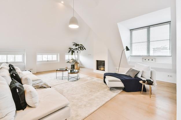 Eigentijds minimalistisch interieur van loungezone met banken en tapijt in open zolderappartement met witte muren en loftstijl