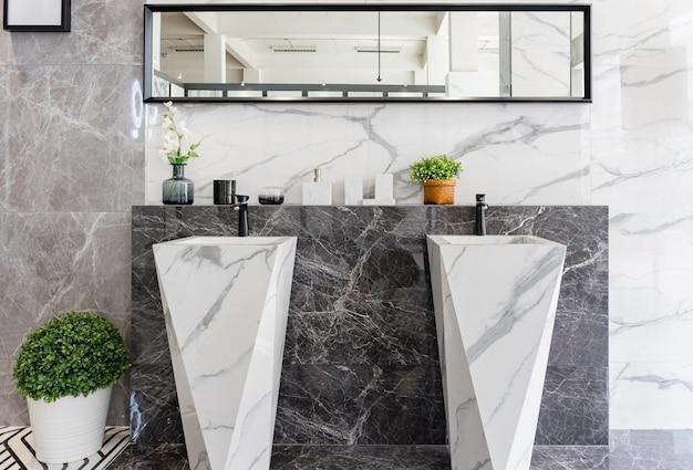 Eigentijds ontworpen badkamer met twee wastafels met zwarte kranen