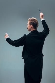 Eigentijdse ballroomdanser die op grijze studiomuur wordt geïsoleerd
