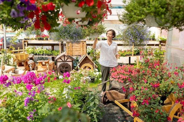 Eigentijdse bloemist of tuinman die door tuincentrum loopt tussen bloeiende bloemen en geniet van hun geur