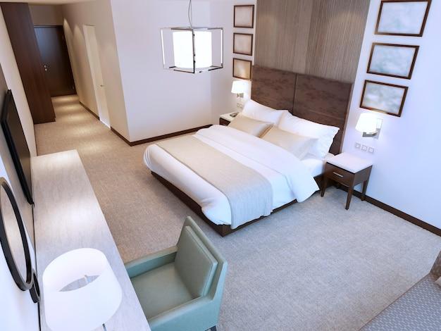 Eigentijdse hotelkamertrend met tweepersoonsbed en kaptafel en tv.