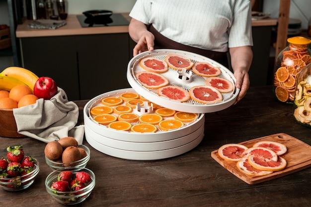 Eigentijdse huisvrouw die zich door keukentafel bevindt en fruitdroogrek met gesneden grapefruit daarop met stukjes sinaasappel zet