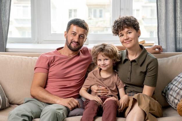 Eigentijdse jonge aanhankelijke familie van moeder, vader en zoontje in broek en t-shirts die in omhelzing op zachte comfortabele bank zitten