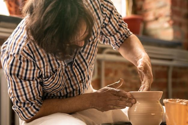 Eigentijdse jonge ambachtsman die door het draaien van aardewerkwiel zit tijdens het vormgeven van ruwe kleipot in zijn atelier