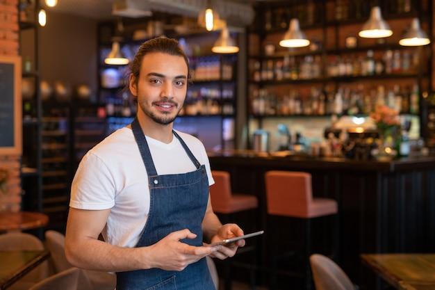 Eigentijdse jonge knappe ober in schort die tablet gebruikt tijdens het opnemen van online bestellingen van klanten die 's avonds komen