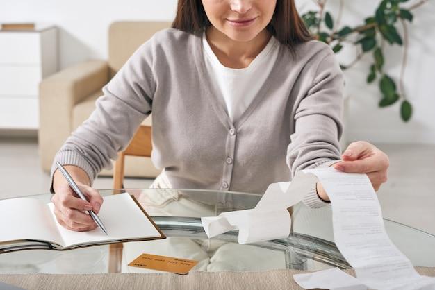 Eigentijdse jonge vrouw die betalingsbewijzen bekijkt en al haar uitgaven in notitieboekje opschrijft