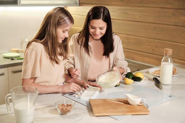 Eigentijdse jonge vrouw en tienermeisje die zelfgemaakt ijs voorbereiden, terwijl een van hen mengsel in siliconenvormen brengt