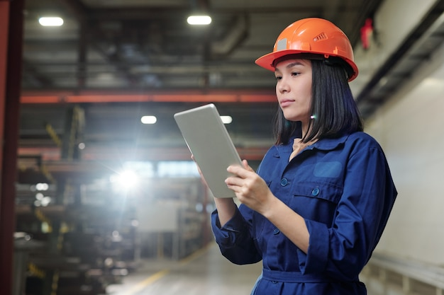 Eigentijdse jonge vrouwelijke ingenieur in veiligheidshelm en blauw uniform touchpad-display kijken tijdens het werken met technische gegevens