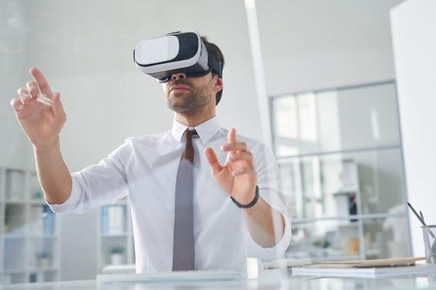 Eigentijdse jonge zakenman virtuele presentatie maken tijdens het werken in kantoor