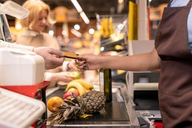 Eigentijdse kassier in bruin schort die terug geeft of creditcard van volwassen cliënt over kassa neemt terwijl hij hem in supermarkt bedient