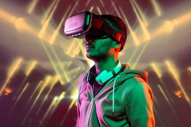 Eigentijdse man in vrijetijdskleding die in de virtuele wereld reist terwijl hij geïsoleerd staat tegen neonlichten