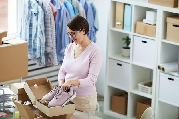 Eigentijdse manager van online winkelkantoor die een paar nieuwe sportschoenen inpakt